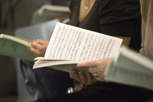 Choir singers female hands holding musical scores