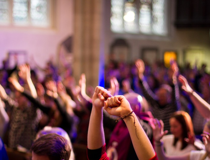 York, United Kingdom - May 15, 2016: A congregation worship with raised hands at a Christian church service held at St Michael Le Belfry.